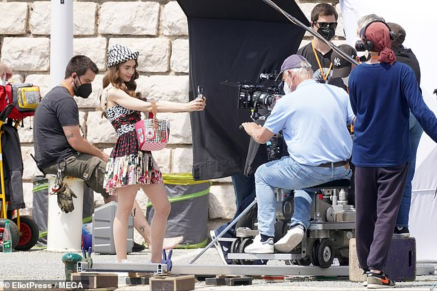 Say cheese: Evidently pleased with the character's latest ensemble, Lily took a series of cheerful selfies while relaxing on the outdoor set