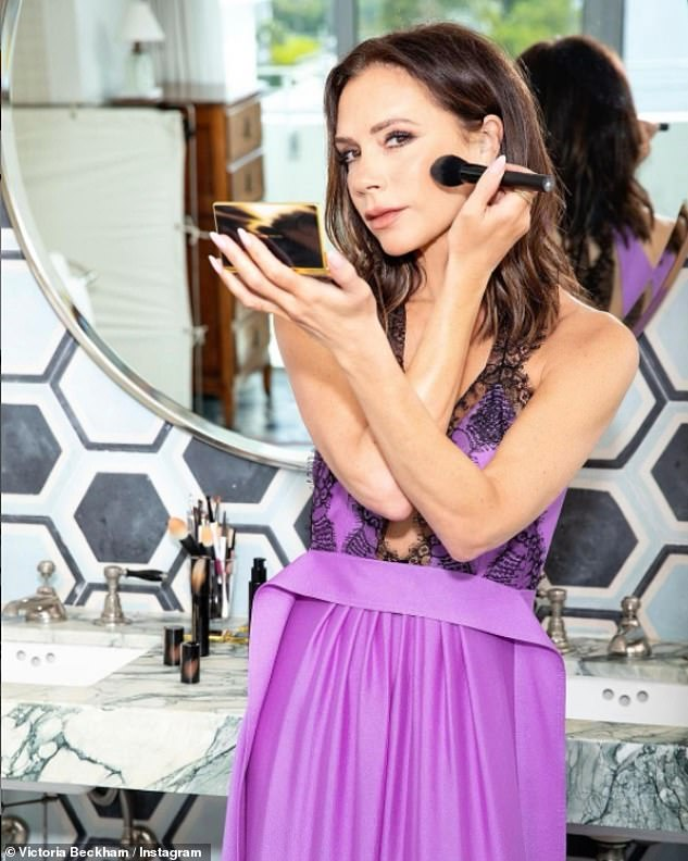 Glowing:The singer turned fashion mogul slipped into the elegant runway number from the comfort of her bathroom as she topped up her radiant make-up for an Instagram video