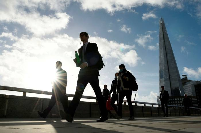 Commuters walk over London Bridge during the morning rush hour, days before the second national lockdown last November