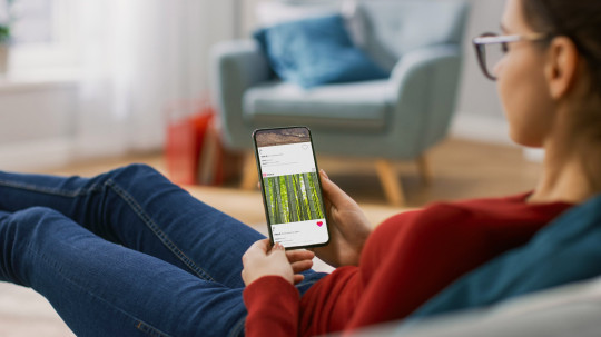 Young Woman at Home Lying on a Couch using Smartphone Scrolling Through Sotcial Media Feed, Doing Swiping, Scrolling Gestures.