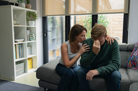woman comforts a crying man