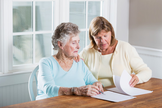 Woman helps her elderly mother sign a contract.