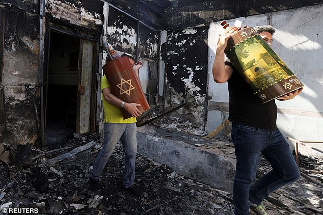 Israeli men carry Torah scrolls from a synagogue in the city of Lod which was torched last night amid rioting. Netanyahu personally visited the central city in the early hours of Wednesday to declare a state of emergency