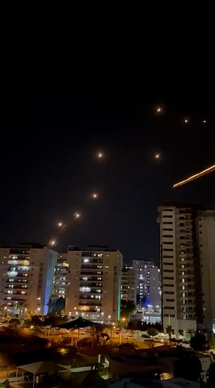 Large bangs can be heard every few seconds, marking the moment a rocket is shot down by the Iron Dome defence system