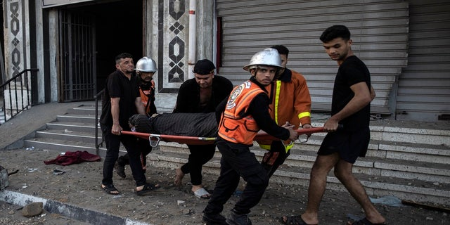 Palestinian rescuers evacuate an elderly woman from a building following Israeli airstrikes on Gaza City on Wednesday. (AP)