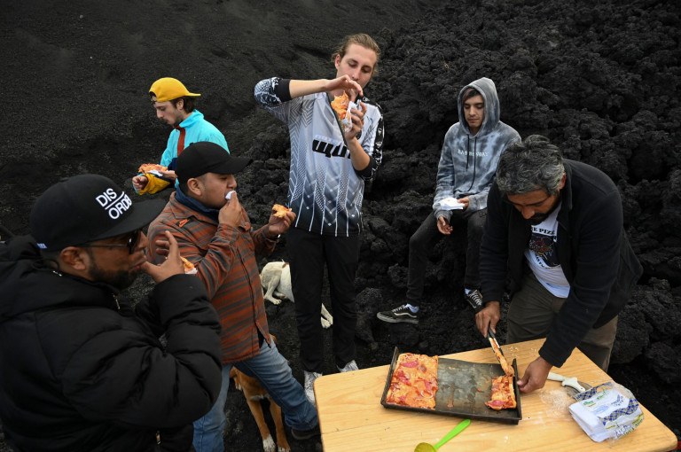 David Garcia serves pizza to tourists after cooking on the lava rivers that come down from the Pacaya volcano at the Cerro Chino hill in San Vicente Pacaya municipality, Guatemala, on May 11, 2021. - Garcia makes a pizza in a very particular oven: an extensive river of lava that springs from the furious Pacaya volcano. (Photo by Johan ORDONEZ / AFP) (Photo by JOHAN ORDONEZ/AFP via Getty Images)