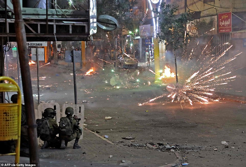 Palestinians clash with Israeli security forces in the city centre of the West Bank town of Hebron on May 12