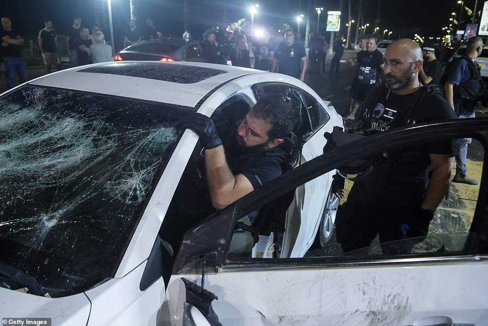 An Israeli police officer inspects the car of an Israeli Arab man who was attacked and injured by an Israeli Jews mob