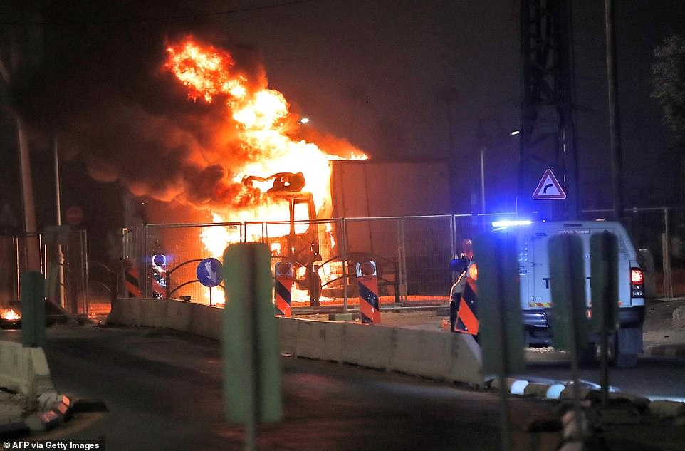 A truck burns in the mixed Jewish-Arab city of Lod, where a state of emergency has been declared following riots