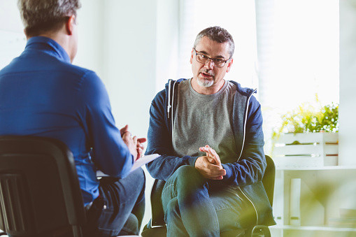 Mature man talking with professional in his office