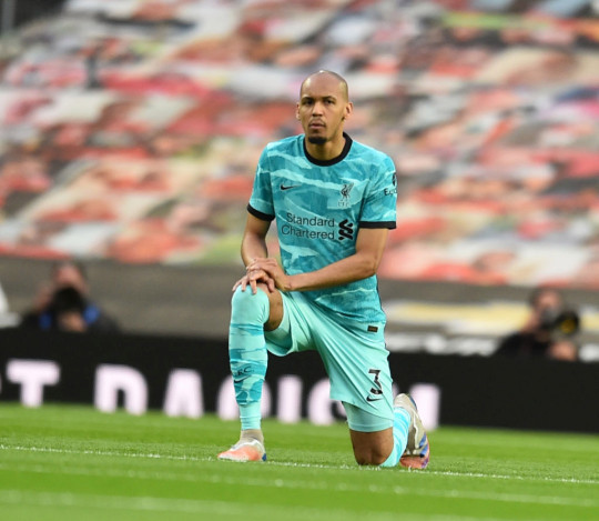 Fabinho of Liverpool takes to the knee before the Premier League match between Manchester United and Liverpool at Old Trafford on May 13, 2021 in Manchester, England. Sporting stadiums around the UK remain under strict restrictions due to the Coronavirus Pandemic as Government social distancing laws prohibit fans inside venues resulting in games being played behind closed doors.