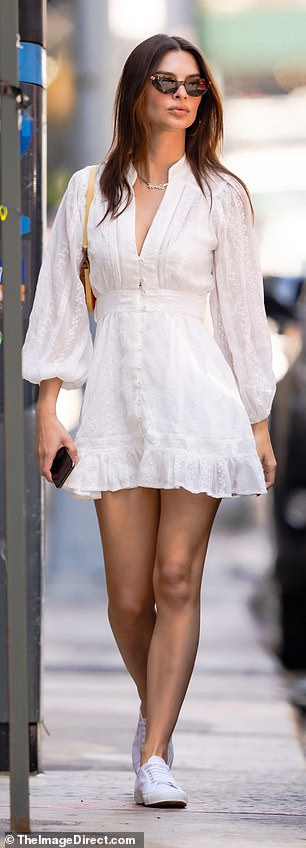 Style star: Emily was the picture of summer style as she took a walk in New York City this week wearing a pair of white trainers that matched her long sleeve white sundress
