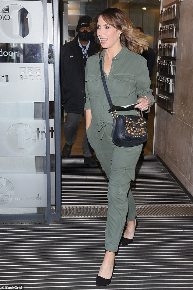 There she is:The star paired her chic maternity outfit with black stilettos and a studded bag