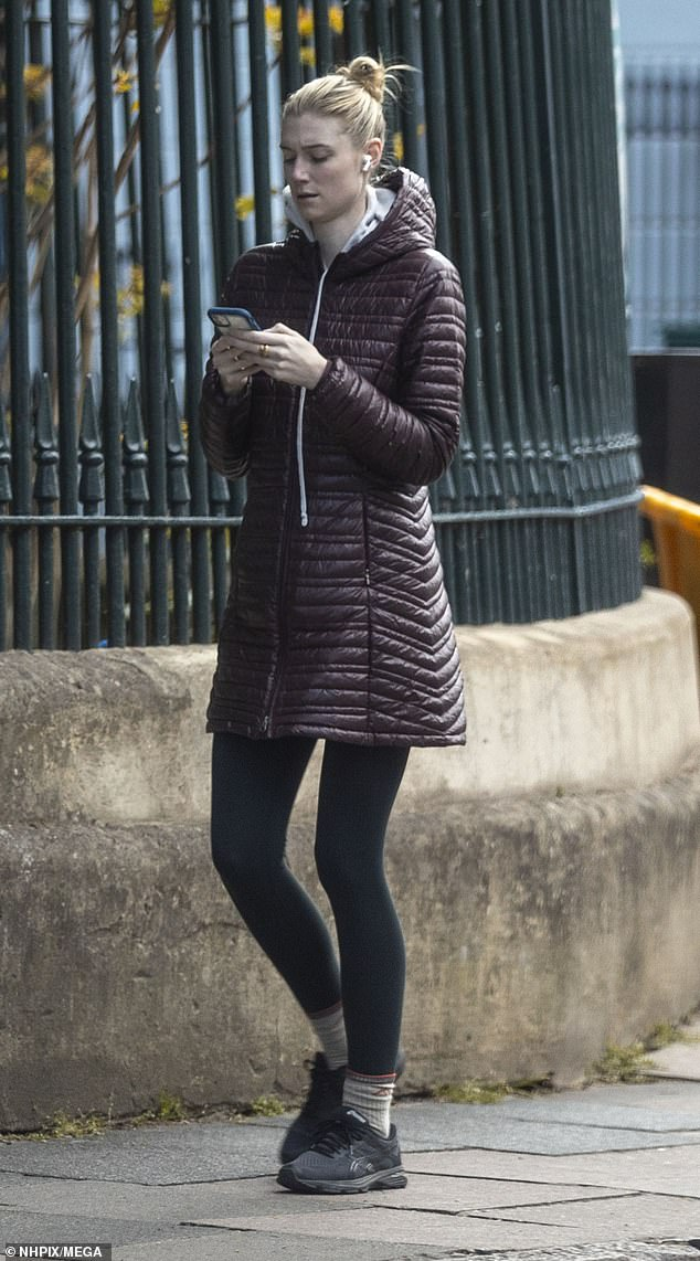 Checking up: Elizabeth bundled up in a padded coat as she checked her phone