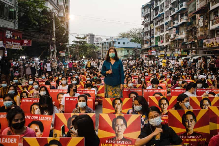 Protesters with placards showing the image of detained Myanmar civilian leader Aung San Suu Kyi sit along a street before holding a candlelight vigil during a demonstration against the military coup in Yangon