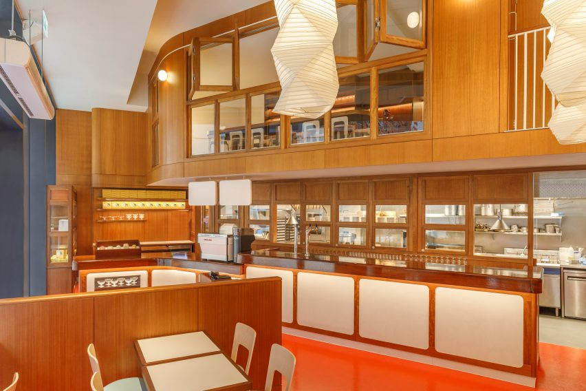 Wood serving counter and glossy red floor in London restaurant by Macaulay Sinclair