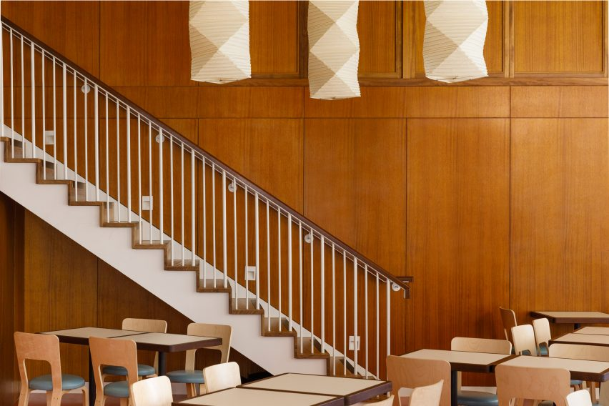 White staircase and wood-panelled walls in London restaurant by Macaulay Sinclair