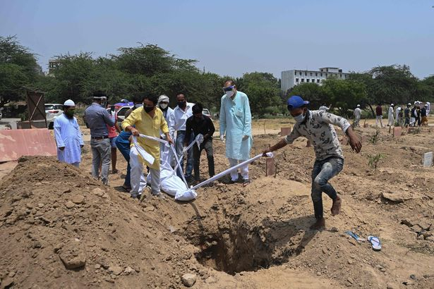 Relatives, friends and graveyard workers prepare to lower the body of a Covid-19 victim at a graveyard in New Delhi on April 28