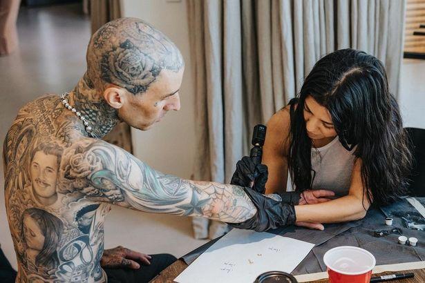 A topless Travis Barker being tattooed by Kourtney Kardashian.