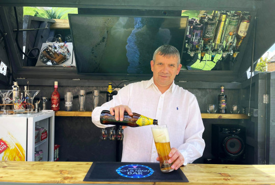 RICHARD WARD / CATERS NEWS (PICTURED- Richard Ward, who built the secret bar with enhanced security, enjoys a pint stood inside) - A dad had built an ordinary shed in his garden which transforms into a secret cocktail bar. Dad-of-three, Richard Ward, from Dinnington, Sheffield, built an unassuming shed in his back garden which has a removable roof. After deciding to build a bar, the 51-year-old decided he wanted it to resemble an ordinary shed for enhanced security and not to attract burglars. But when the roof of the discreet bar opens up, the trendy cocktail bar is uncovered and its height increases to over 7ft with ample space for two people to stand inside. - SEE CATERS COPY
