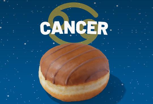 A Greggs custard doughnut with the word Cancer above it.