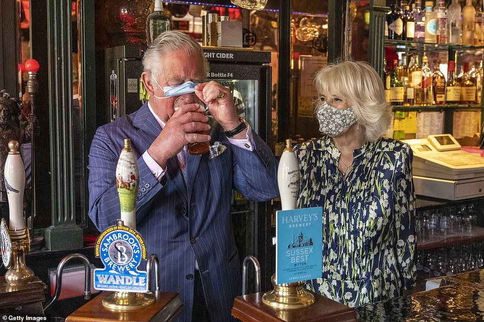 Prince Charles, Prince of Wales adjusts his face mask to enable him to sip a pint that he pulled in a pub alongside Camilla, Duchess of Cornwall during a visit to Clapham Old Town as Britain continues easing restrictions
