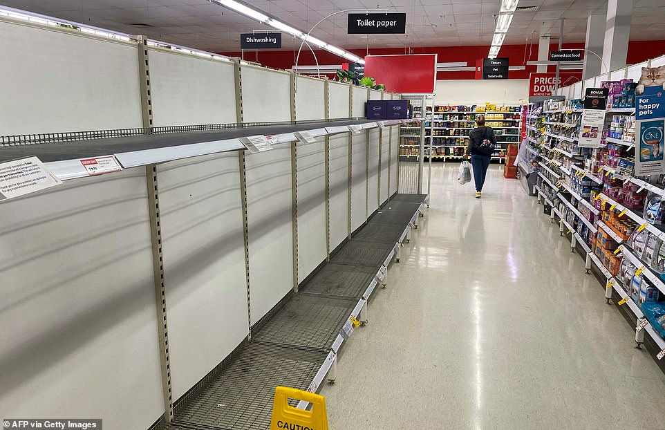 A shopper walks past empty toilet paper shelves in a Melbourne supermarket on Thursday, as the city's residents returned to a seven day lockdown to curb the spread of the Covid-19 coronavirus