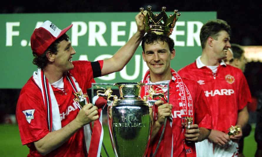 Steve Bruce crowns Bryan Robson after Manchester United win the Premier League in May 1993.