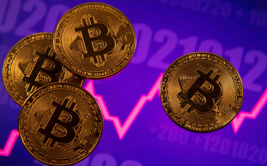 FILE PHOTO: A representation of virtual currency Bitcoin is seen in front of a stock graph in this illustration taken March 15, 2021. REUTERS/Dado Ruvic/Illustration/File Photo