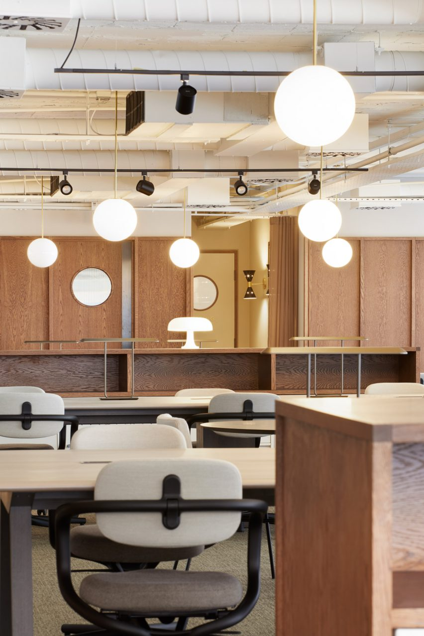 Spherical lights in wood-panelled office by dMFK Architects