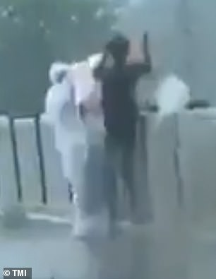 The video, taken on Friday, shows two people, one wearing full protective clothing, hoisting the wrapped corpse over the side of the bridge