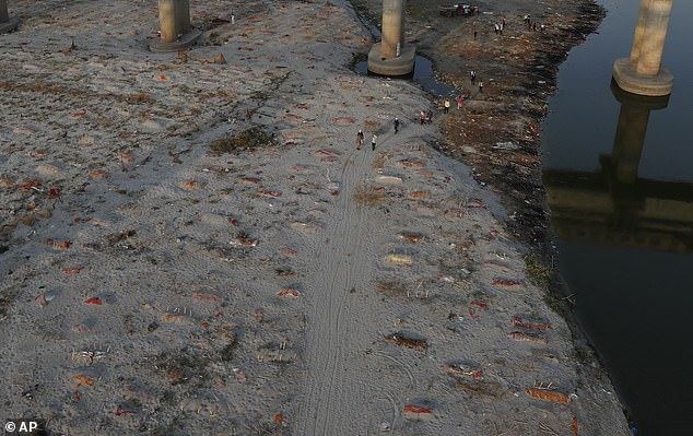 Rains exposed the cloth coverings of bodies buried in shallow graves in the sand of the riverbank in Prayagraj, a city in Uttar Pradesh state