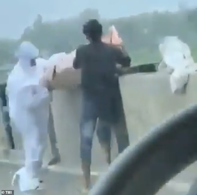 A Covid vicitm's body was dumped into an Indian river by relatives wearing PPE in shocking footage showing the devastating toll of the pandemic