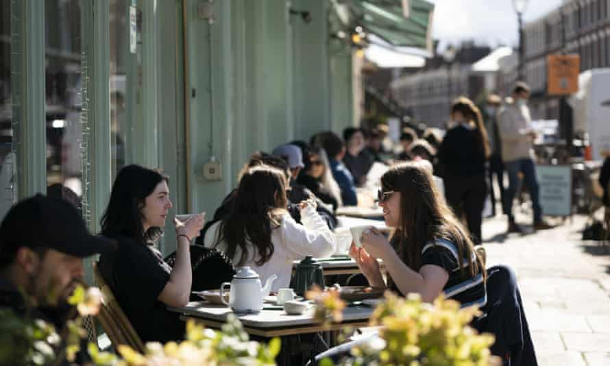 People drink tea outside a restaurant in Liverpool.