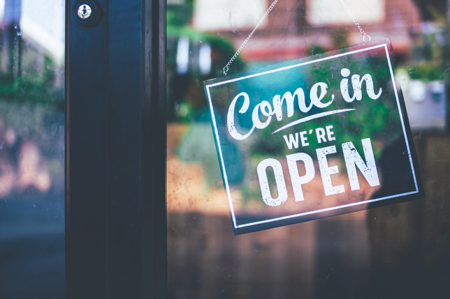 Come in we're open, vintage black retro sign on a glass door,