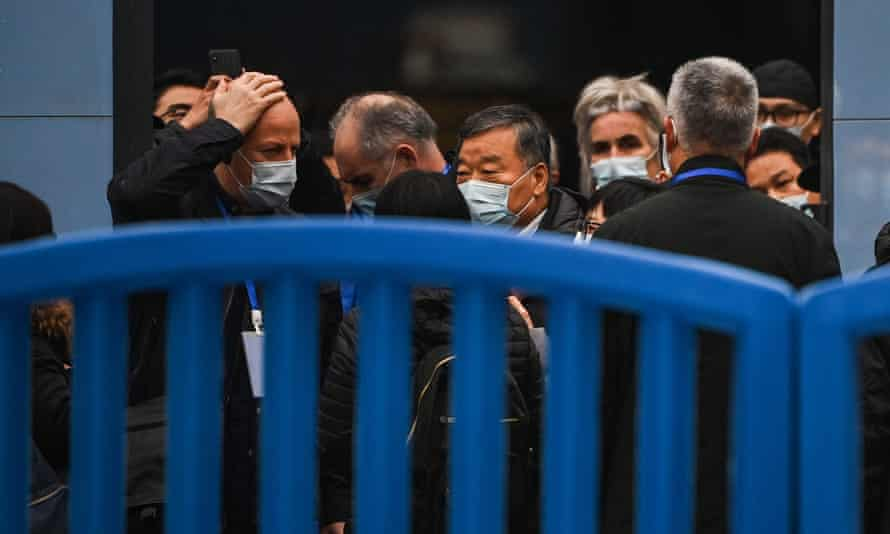 people in masks behind a security barrier