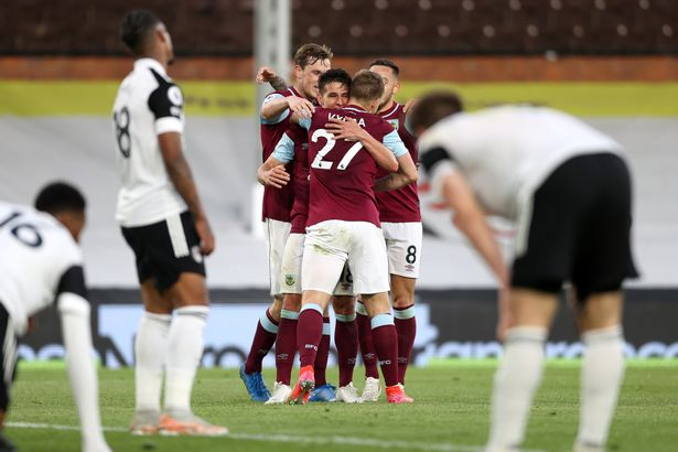 Burnley's players celebrate their opening goal as Fulham stars look on dejected