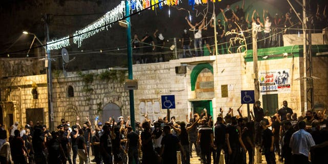 Israeli Arabs gather next to a mosque during clashes between Jews, Israeli police and Arabs, in the mixed town of Lod, central Israel, Wednesday, May 12, 2021.