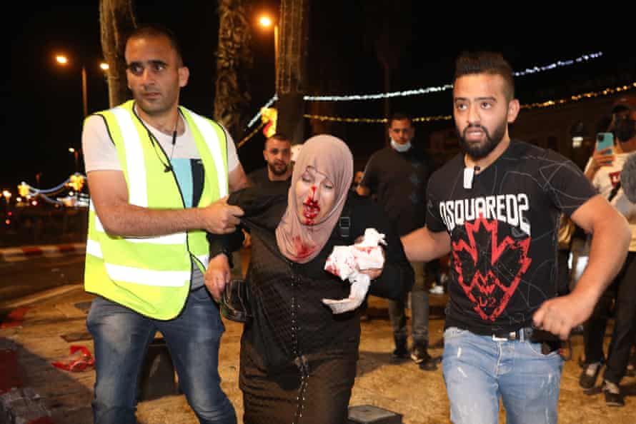 People help an injured Palestinian woman during a protest in Damascus gate supporting Palestinian families that face eviction from their homes at Sheikh Jarrah neighborhood, in Jerusalem.