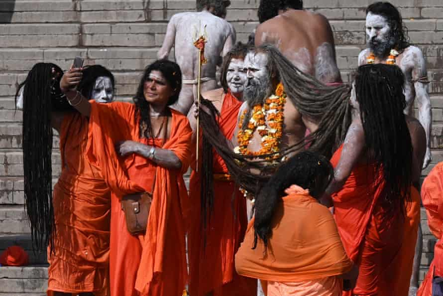 Naga sadhus (Hindu holy men and women) take pictures after taking a dip in the waters of the Ganges during Kumbh Mela in Haridwar.