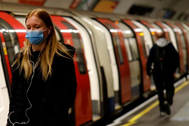 People wear masks at a Tube station