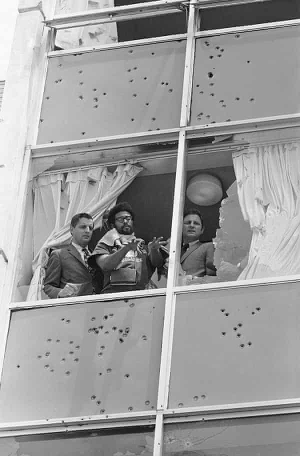 On 20 May 1970, Democratic senators Walter Mondale and Birch Bayh look from the shattered windows of Alexander Hall.