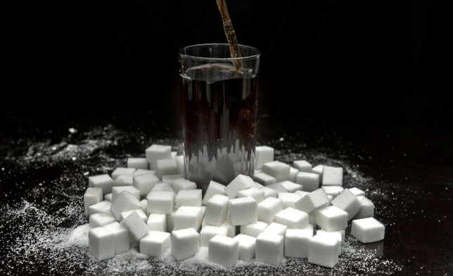 EMBARGOED TO 2330 THURSDAY MAY 6 File photo dated 22/7/2015 of a cola carbonated drink surrounded by sugar cubes. Drinking two or more sugary drinks a day could increase the risk of bowel cancer among women under the age of 50, a new study suggests. Issue date: Thursday May 6, 2021. PA Photo. Researchers found that each daily serving was associated with a 16% higher risk. Replacing sugar-sweetened beverages with artificially sweetened drinks, coffee or milk actually led to a lower risk of disease, the study found. See PA story HEALTH Sugar. Photo credit should read: Anthony Devlin/PA Wire
