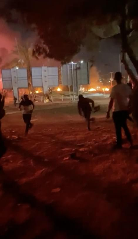 Arabs and Israelis can be seen running away from gunfire amid burning buildings in Lod last night. Residents say there is little effective policing to help them with the situation