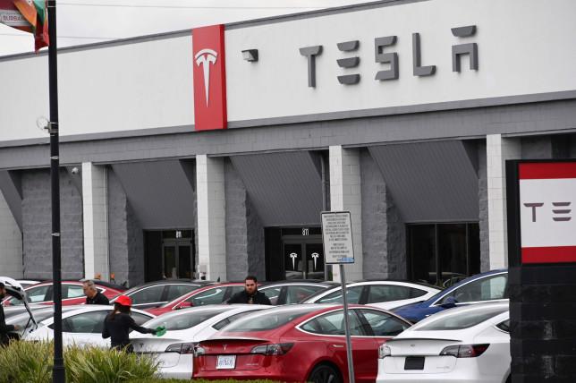 Telsa employees work outside a Tesla showroom in Burbank, California. (AFP)