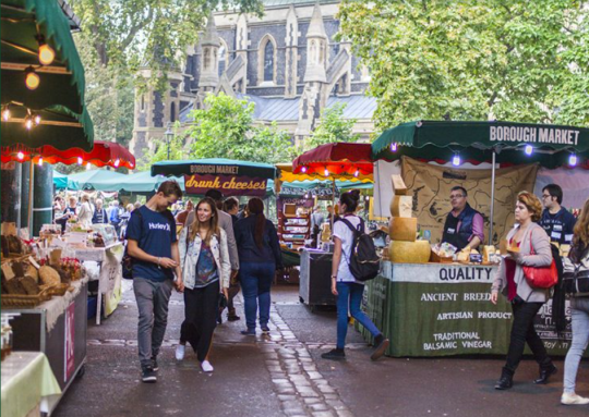 Groups of people shopping outside at market stalls in London