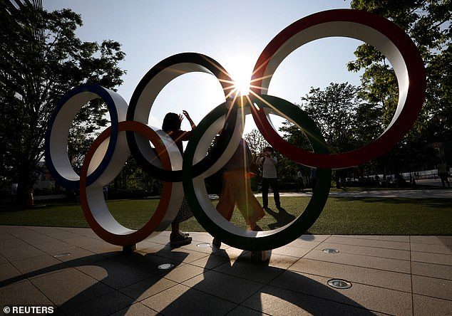 Tokyo Olympics fans may have to be vaccinated or test negative for the coronavirus before being allowed into venues. Pictured: the Olympic Rings outside the Japan Olympic Committee
