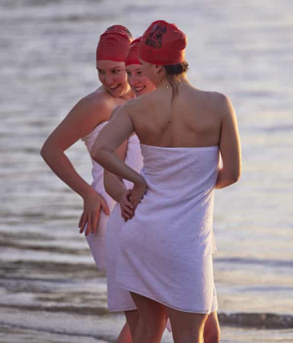 Three swimmers pose in their towels after the event at Sandy Bay Beach.