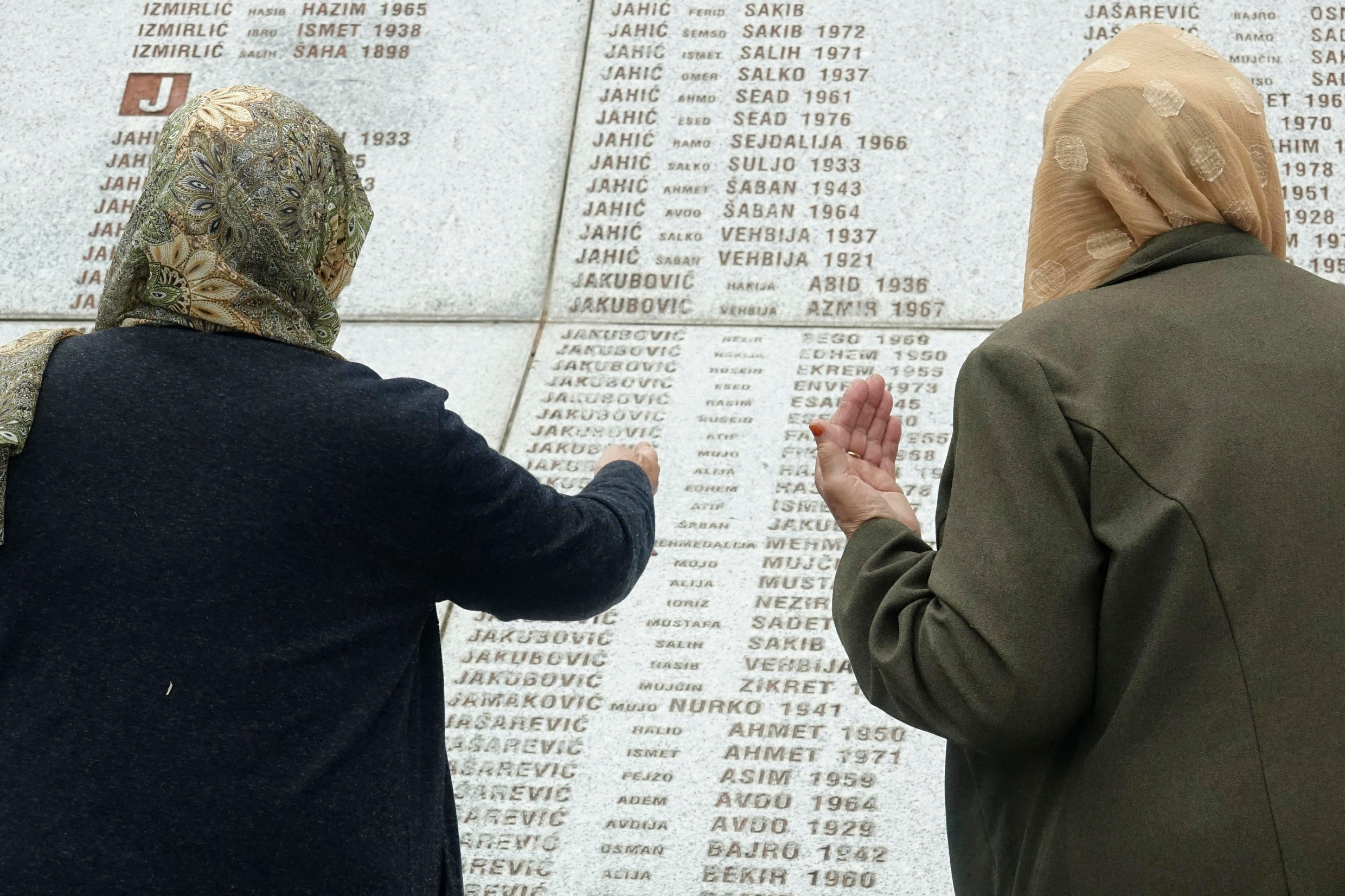 Women who lost their relatives in the Srebrenica massacre look at names at the memorial cemetery in nearby Potocari on May 28, 2021.