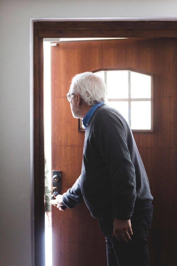 An elderly man leaving the house